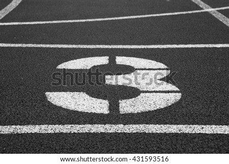 Number three. White track number on red rubber racetrack, texture of racetracks in outdoor stadium. Black and white photo - stock photo