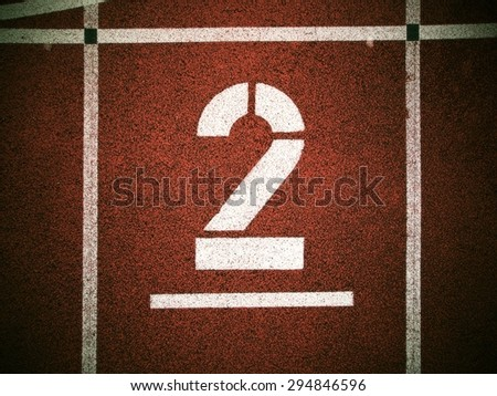 Number two. Big white track number on red rubber racetrack. Gentle textured running racetracks in small outdoor stadium. - stock photo