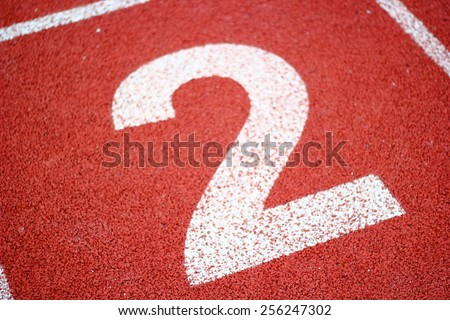 Number two  on athletics all weather running track/Number two On Running Track - stock photo