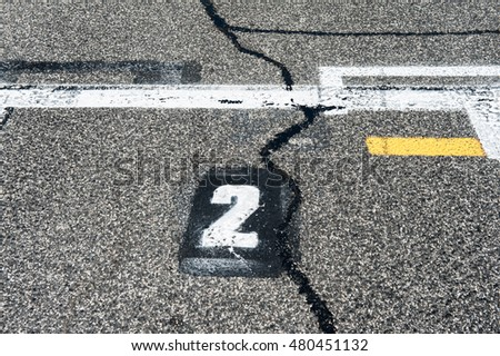 Number two position sign on speedway starting track with yellow line and damaged old asphalt