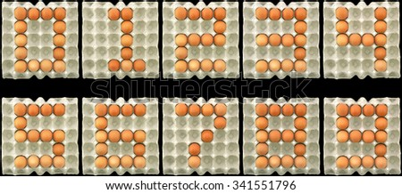 Number zero one two three four five six seven eight nine ten show by eggs in paper tray isolated on black background - stock photo