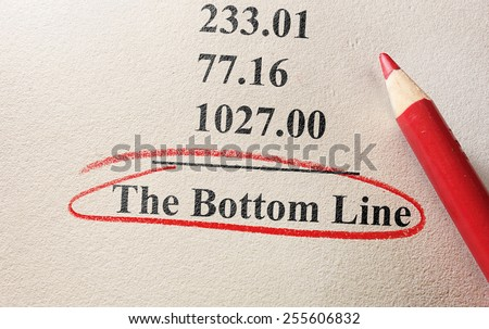 numbers and pencil with The Bottom Line circled                                - stock photo