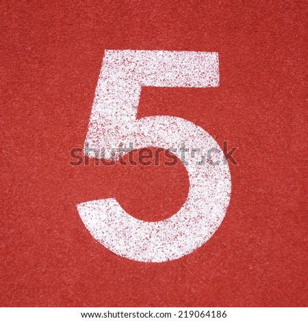 Numbers five on red running track - stock photo