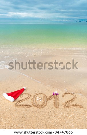 Numbers 2012 on tropical beach sand - vertical holiday background - stock photo
