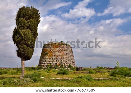 Nuraghe tower ruins and pine tree Sardinia Sardegna Italy archeological remnants of prehistoric building of bronze age ancient civilization tourism and archeology