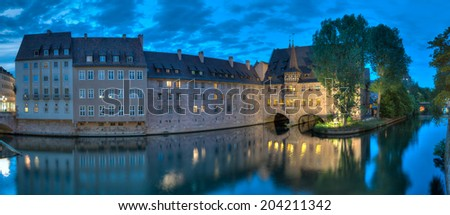 Nuremberg panorama at night along the river Pegnitz from the Museumsbruecke to the Heilig-Geist-Spital. - stock photo