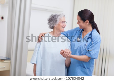 Nurse and a patient standing in hospital ward - stock photo