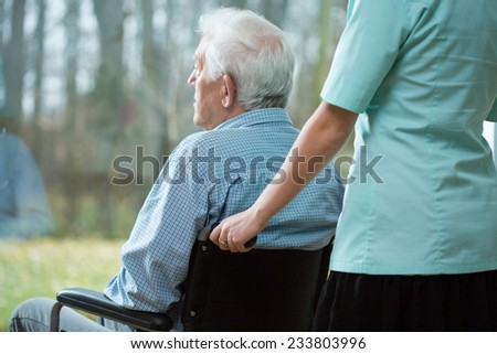 Nurse and handicapped man looking from the window - stock photo