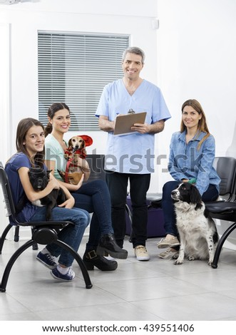Nurse And Owners With Pets In Clinic's Waiting Area - stock photo