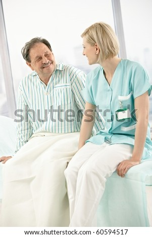 Nurse and patient sitting on hospital bed together, chatting, smiling.? - stock photo