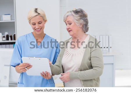 Nurse and senior patient discussing over clipboard in clinic - stock photo