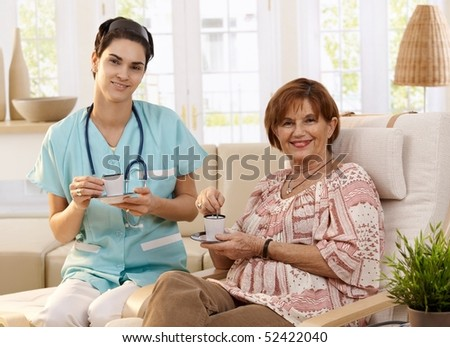 Nurse and senior patient drinking coffee after examination at home, smiling. - stock photo