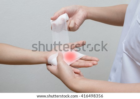 Nurse applying bandage to patient injured hand - stock photo