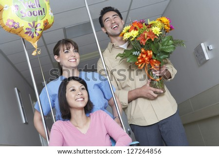 Nurse assisting female patient on wheelchair while leaving hospital with man - stock photo