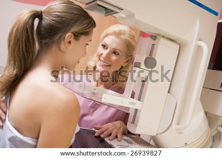 Nurse Assisting Patient Undergoing Mammogram - stock photo