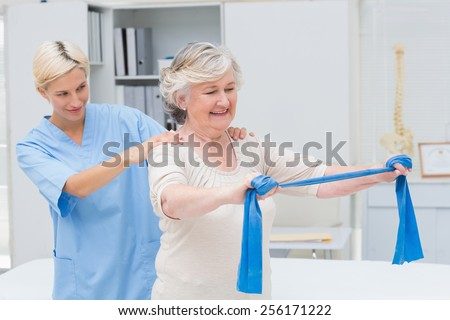 Nurse assisting senior patient in exercising with resistance band in clinic - stock photo