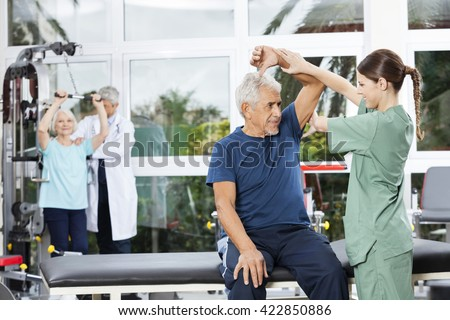 Nurse Assisting Senior Woman In Arm Exercise In Rehab Center - stock photo