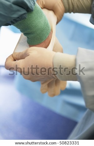 Nurse assisting surgeon Putting on Sterile Latex Gloves, close up of hands - stock photo