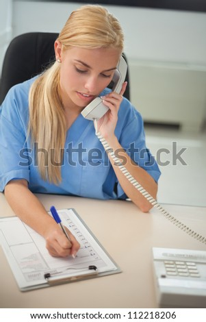 Nurse calling while writing on a clipboard in hospital reception - stock photo