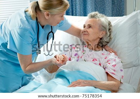 Nurse cares for a elderly woman lying in bed - stock photo