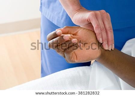 Nurse checking patients pulse - stock photo