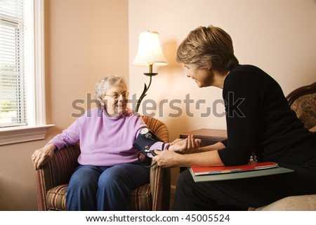 Nurse checks an elderly woman's blood pressure in an assisted living home.  Horizontal shot. - stock photo