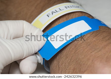 Nurse checks hospital patient identification bracelet. - stock photo