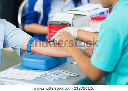 Nurse collecting a blood from a patient for annual check - stock photo