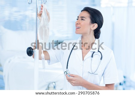 Nurse connecting an intravenous drip in hospital room - stock photo