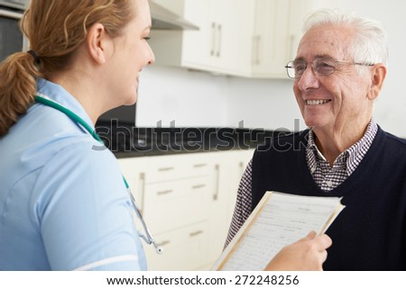 Nurse Discussing Medical Record With Senior Male Patient - stock photo