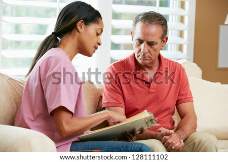 Nurse Discussing Records With Senior Male Patient During Home Visit - stock photo