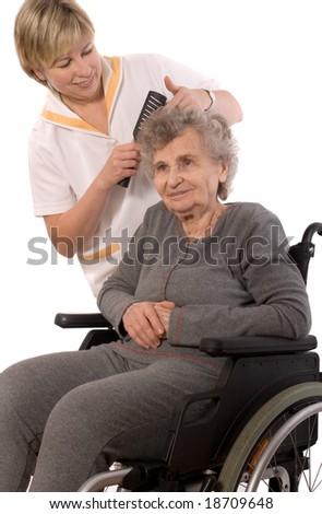 Nurse dressing the hair of a senior woman - stock photo