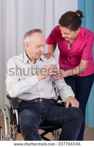 Nurse gives a cup of water a disabled man