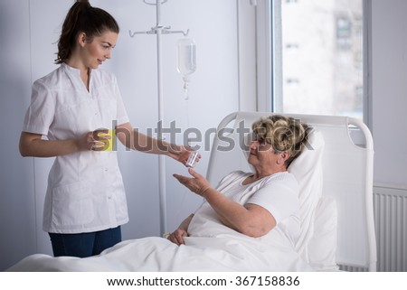 Nurse giving medicine to elderly hospice patient - stock photo