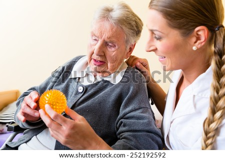 Nurse giving physical therapy with massage ball to senior woman in wheelchair - stock photo
