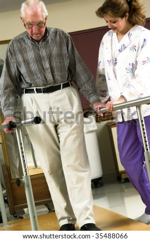 nurse helping senior man with physical rehabilitation - stock photo