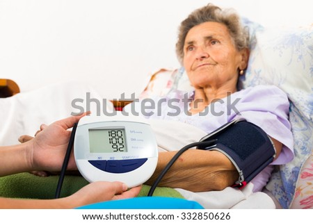 Nurse helping to measure patient's blood pressure with digital device. - stock photo