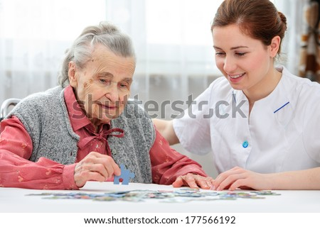 Nurse helps the senior woman jigsaw puzzle to solve in a nursing home - stock photo