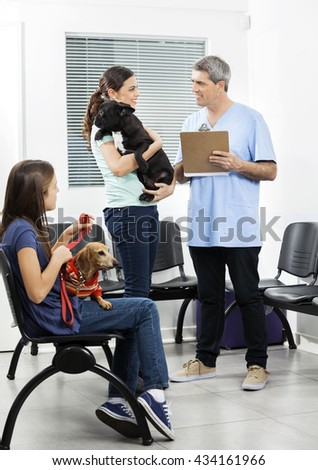 Nurse Holding Clipboard While Pet Owners Looking At Him - stock photo