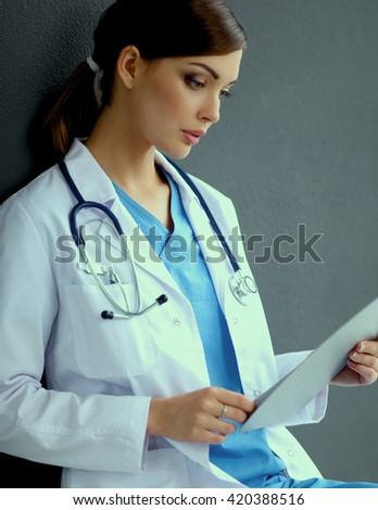 Nurse holding folder and taking notes - sitting  on grey background - stock photo