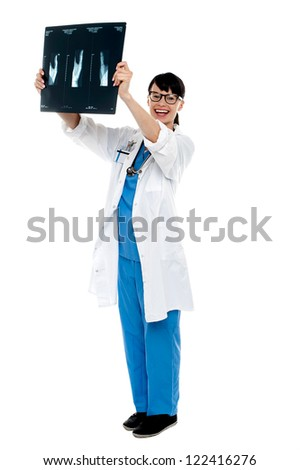 Nurse holding x-ray sheet against light to examine the same. Full length shot. - stock photo