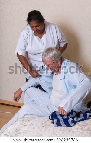 Nurse in nursing home helping elderly man getting dressed - stock photo