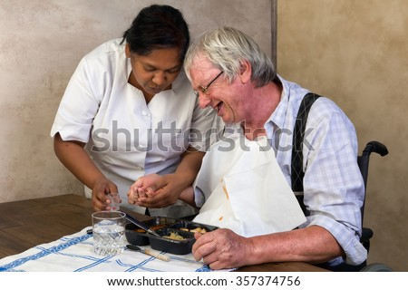Nurse in old people's home trying to make a patient eat his dinner and pills - stock photo