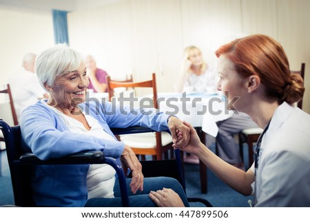 Nurse interacting with a senior woman in wheelchair in the retirement house - stock photo