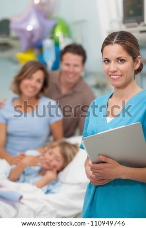 Nurse looking at camera next to a family in hospital ward - stock photo