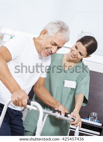 Nurse Looking At Senior Patient Using Walker In Rehab Center - stock photo