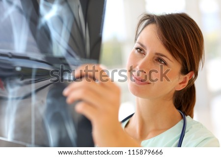 Nurse looking at X-ray results - stock photo