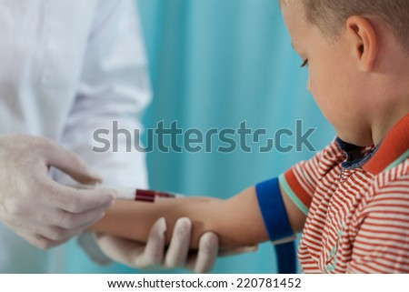 Nurse making boy blood sampling to test his health  - stock photo