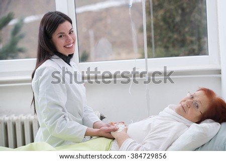 Nurse or doctor cares for a elderly woman lying in bed - stock photo