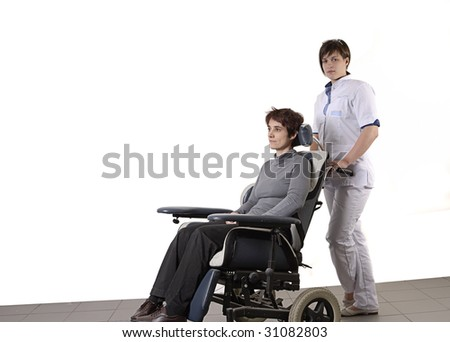nurse pushing a disabled woman in a wheelchair - stock photo